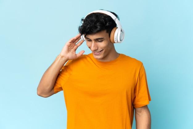 Giovane uomo argentino isolato sulla musica d'ascolto della parete