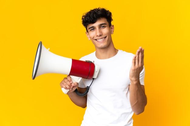 Giovane argentino isolato su sfondo giallo che tiene in mano un megafono e invita a venire con la mano
