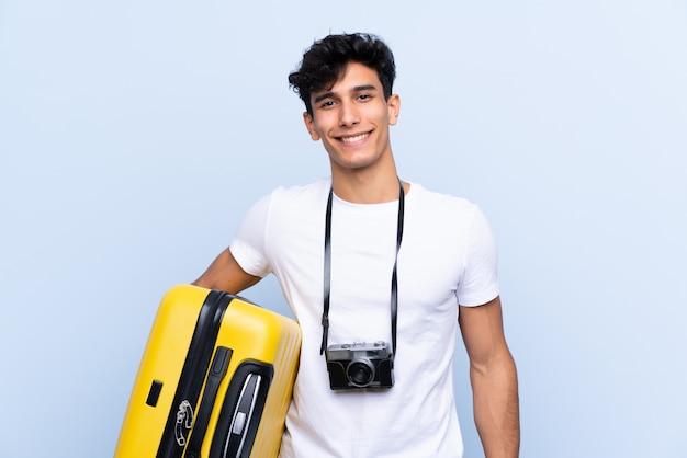 Giovane uomo argentino del viaggiatore sopra la parete blu isolata che sorride molto