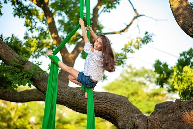 Giovane atleta di ginnastica arial e vista sull'albero
