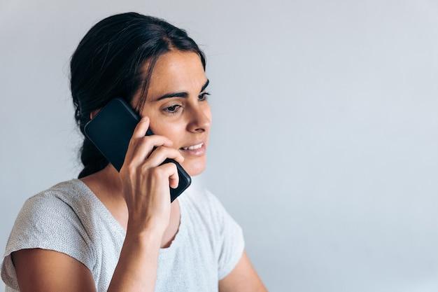Giovane donna artigiana che lavora da casa e parla al telefono su sfondo bianco.