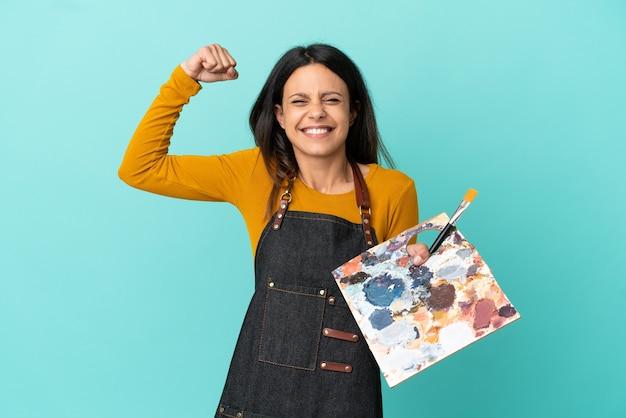 Giovane artista donna caucasica che tiene una tavolozza isolata su sfondo blu facendo un gesto forte