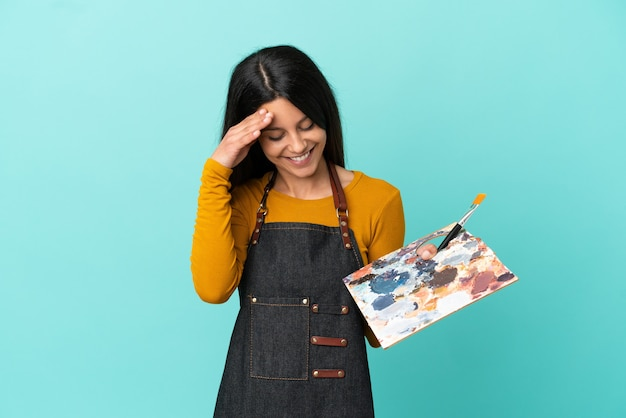 Donna caucasica del giovane artista che tiene una tavolozza isolata su fondo blu che ride