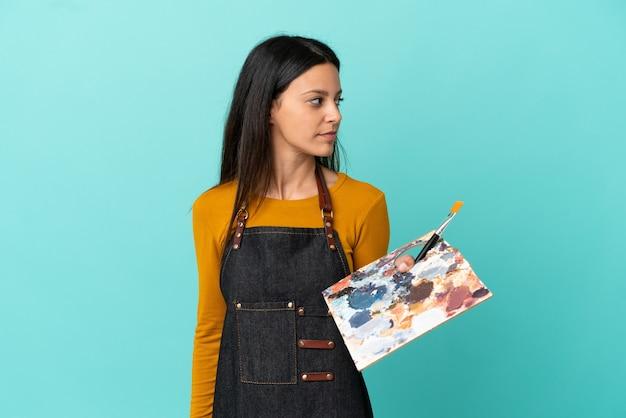 Donna caucasica del giovane artista che tiene una tavolozza isolata su fondo blu che guarda al lato
