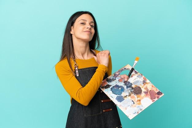 Giovane artista donna caucasica che tiene una tavolozza isolata su sfondo blu orgogliosa e soddisfatta di sé