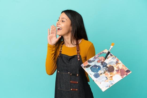 Giovane artista donna caucasica che tiene una tavolozza isolata su sfondo blu che grida con la bocca spalancata di lato