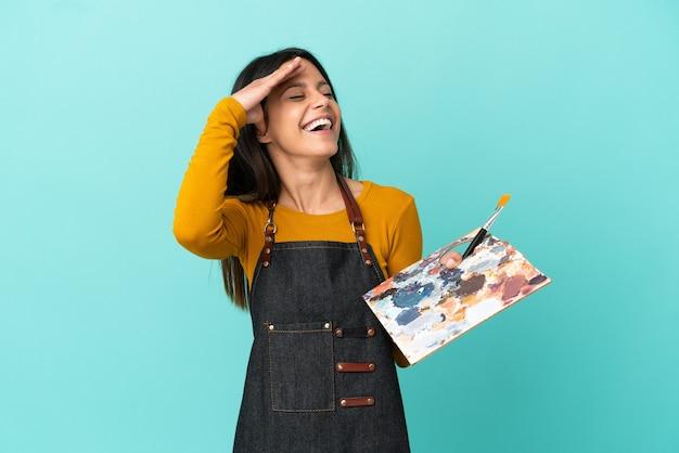 Donna caucasica del giovane artista che tiene una tavolozza isolata su fondo blu che sorride molto