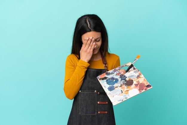 Giovane artista caucasica donna che tiene una tavolozza isolata su sfondo blu con espressione stanca e malata