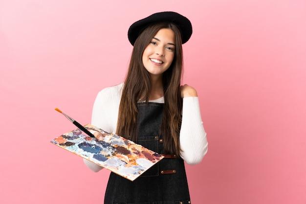 Ragazza giovane artista che tiene una tavolozza su sfondo rosa isolato ridendo