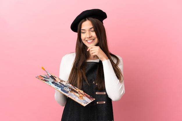 Ragazza giovane artista che tiene una tavolozza su sfondo rosa isolato guardando di lato e sorridente