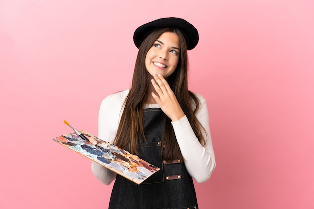 Ragazza giovane artista che tiene una tavolozza su sfondo rosa isolato guardando in alto mentre sorride