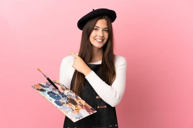 Ragazza del giovane artista che tiene una tavolozza sopra fondo rosa isolato che indica al lato per presentare un prodotto