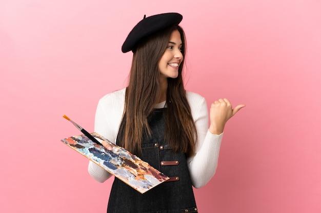Ragazza giovane artista che tiene una tavolozza su sfondo rosa isolato che punta al lato per presentare un prodotto
