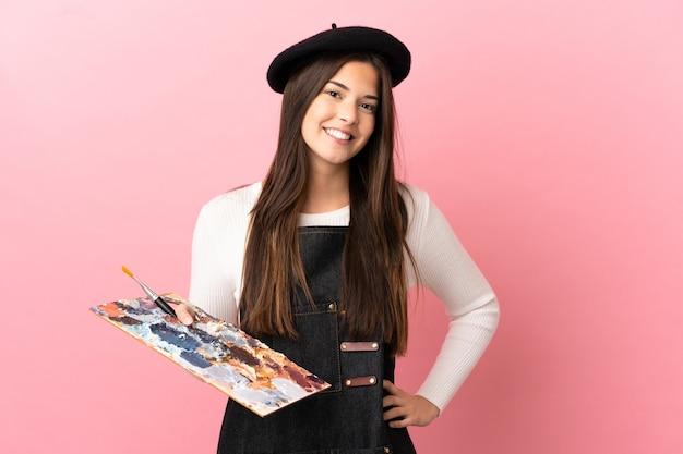 Ragazza giovane artista con una tavolozza su sfondo rosa isolato in posa con le braccia al fianco e sorridente