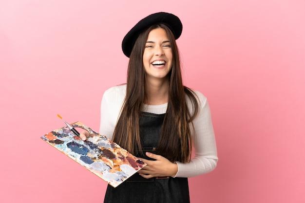 Ragazza giovane artista che tiene una tavolozza su sfondo rosa isolato che sorride molto
