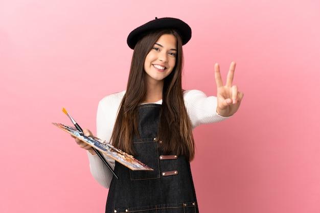 Ragazza giovane artista che tiene una tavolozza su sfondo rosa isolato che sorride e mostra il segno della vittoria