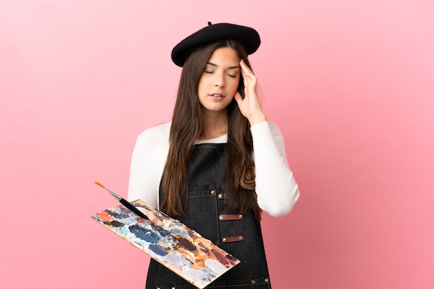 Ragazza giovane artista che tiene una tavolozza su sfondo rosa isolato con mal di testa