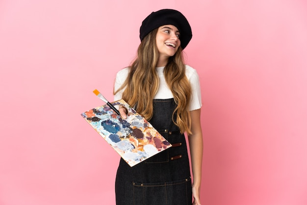 Giovane donna dell'artista che tiene una tavolozza isolata sulla risata rosa