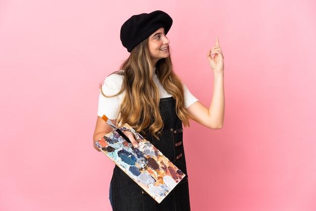Giovane donna dell'artista che tiene una tavolozza isolata sul colore rosa che indica su una grande idea