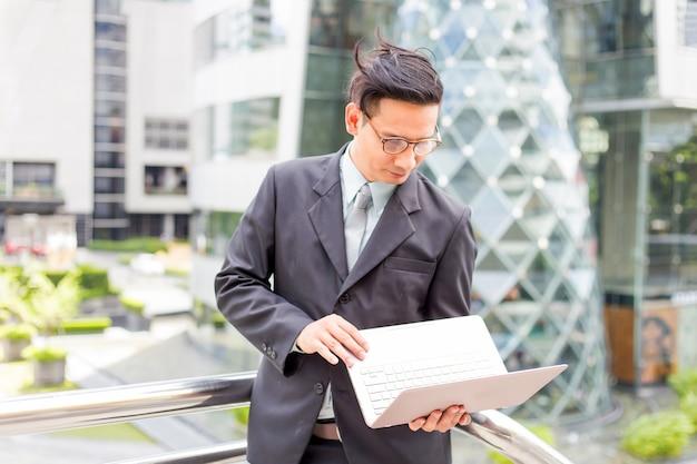 Giovane uomo d'affari dell'asia in vestito con il suo computer portatile all'aperto, costruzione moderna