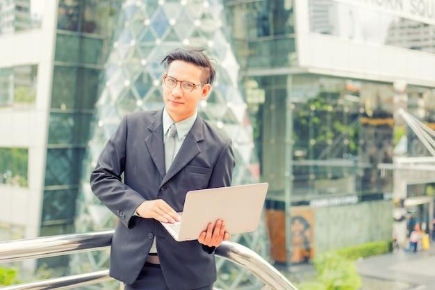 Giovane uomo d'affari dell'asia in vestito con il suo computer portatile all'aperto, costruzione moderna sul