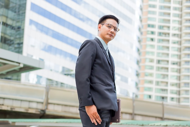 Giovane uomo d'affari dell'asia in vestito con il suo computer portatile all'aperto