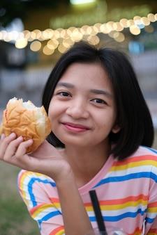 La giovane ragazza asiatica si diverte a mangiare il pane con lo sfondo del bokeh