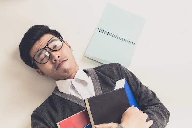 Il giovane studente laureato in asia dorme con il suo libro.