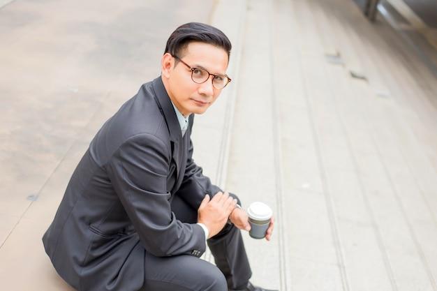 Giovane uomo d'affari bello dell'asia che beve caffè caldo nella città moderna. rompere e rilassarsi il concetto di business