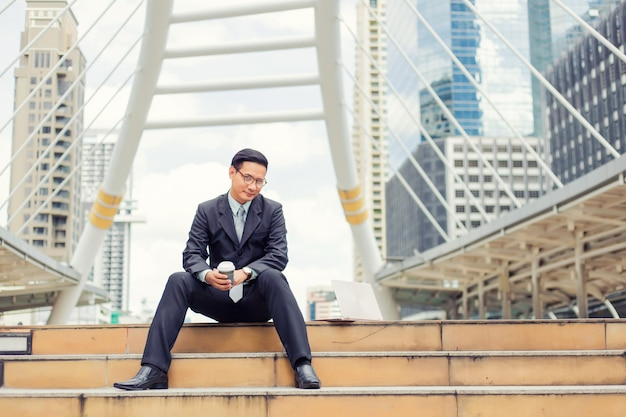 Uomo d'affari bello del giovane asia che beve caffè caldo nella città moderna.