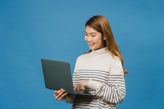 La giovane donna asiatica che usa il computer portatile con un'espressione positiva, sorride ampiamente, vestita con abiti casual sentendosi felice e stando isolata sul muro blu
