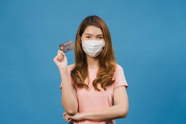 La giovane donna asiatica che indossa una maschera medica mostra la carta di credito con espressione positiva, sorride ampiamente, vestita con abiti casual sentendosi felice e stando isolata sul muro blu