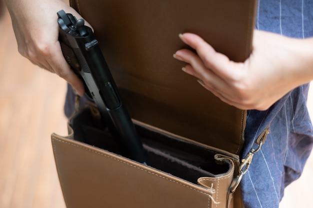 Giovane donna asiatica che mette una pistola nella borsa mano di donna che estrae una pistola dalla borsa