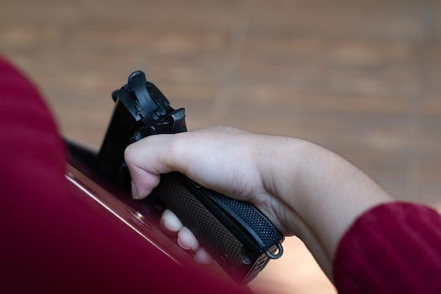 Giovane donna asiatica che mette una pistola nella sua borsetta