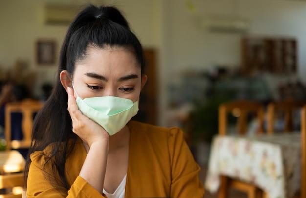 Giovane donna dell'asia che si siede e che indossa una maschera medica per proteggere dalle infezioni respiratorie disperse nell'aria da virus al caffè, copia spec