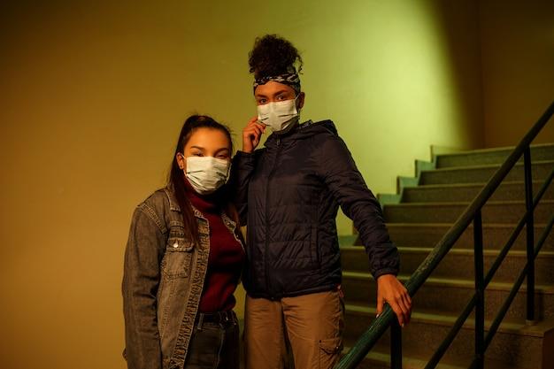 Giovane ragazza asiatica e africana in maschere protettive mediche monouso sul vano scala