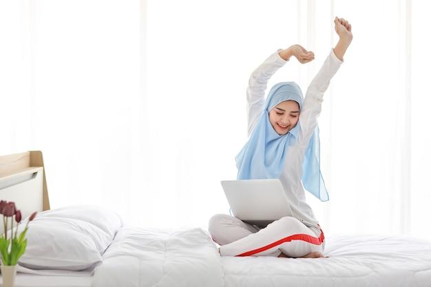 Giovane donna araba asiatica utilizzando laptop seduto sul letto in camera da letto.