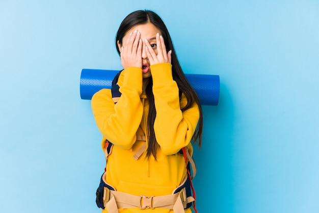 La giovane donna asiatica di viaggiatore con zaino e sacco a pelo sbatte le palpebre spaventata e nervosa