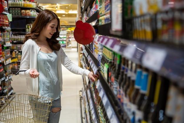 Giovane bello canestro di drogheria asiatico della tenuta che cammina nel supermercato. la scelta di bevande giornaliere nel centro commerciale