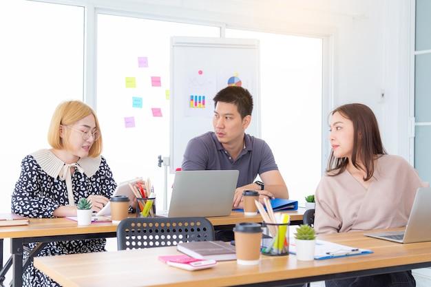 Giovane bella donna asiatica che gesticola e discute di qualcosa mentre i suoi colleghi la ascoltano seduta al tavolo dell'ufficio