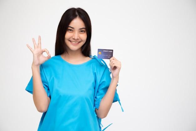 Giovane paziente asiatico della bella donna che mostra la carta di credito di assicurazione contro gli infortuni personale e segno giusto isolati, pa e concetto di servizi dell'indennità sanitaria