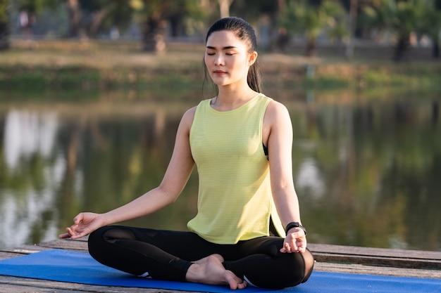 Giovane bella donna asiatica che pratica yoga e medita nella posa del loto all'aperto accanto al lago al mattino per il relax e la pace della mente. armonia e concetto di meditazione. uno stile di vita sano