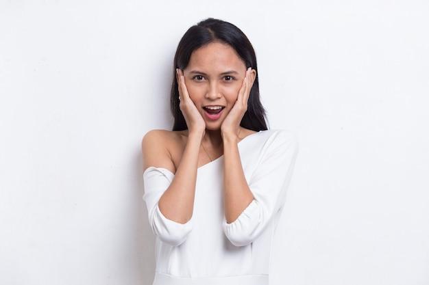 Giovane bella donna asiatica scioccata che copre la bocca con le mani per errore concetto segreto