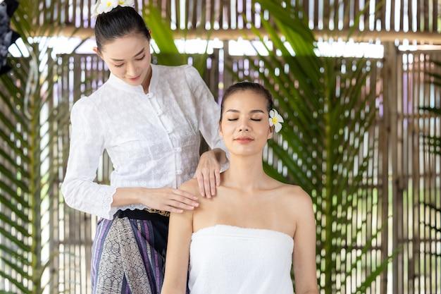 Giovane bella donna asiatica nella spa, massaggio tailandese naturale nella spa, donna asiatica sul lettino da massaggio relax e stile di vita, cura del corpo, corpo termale, massaggio alle mani, donna che fa massaggi nel salone della spa.