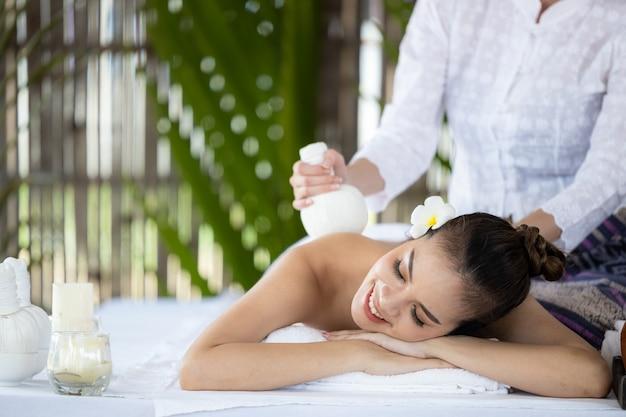 Giovane bella donna asiatica nella spa, massaggio tailandese naturale nella spa, donna asiatica sul lettino da massaggio relax e stile di vita, cura del corpo, corpo termale, massaggio alle mani, donna che fa massaggi nel salone della spa. Foto Premium
