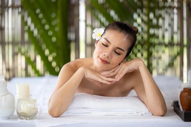 Giovane bella donna asiatica nella spa, massaggio tailandese naturale nella spa, donna asiatica sul lettino da massaggio relax e stile di vita, spa tailandese sano e stile di vita.