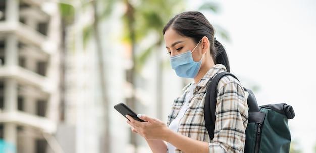Giovani viaggiatori asiatici bella donna utilizzando il suo smartphone