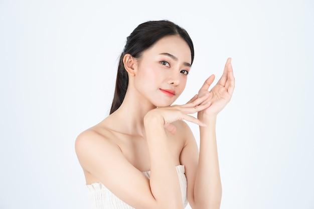La giovane bella donna asiatica in maglietta bianca, ha la pelle sana e luminosa.