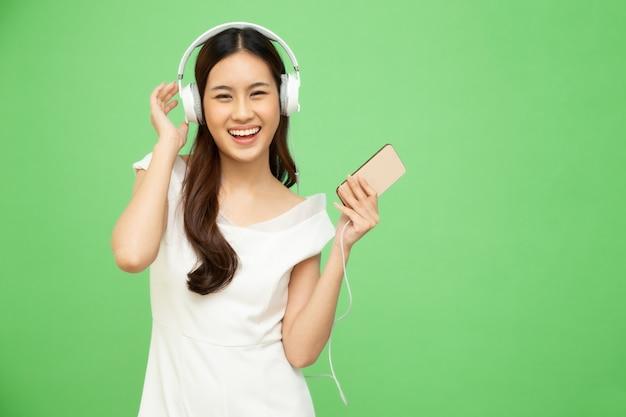 Musica danzante e d'ascolto della giovane donna asiatica di bellezza con le cuffie nell'applicazione di canzone della playlist sullo smartphone isolato sulla parete verde