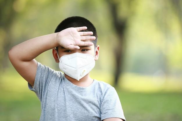 Giovane ragazzo asiatico, indossa una maschera per proteggere dalla polvere pm 2.5 e dai germi